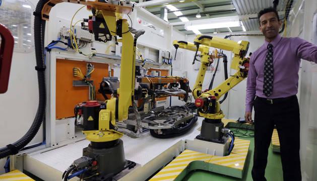 Désiré Cahigiro, director gerente de Uscal, en una de las máquinas que fabrica la empresa. Esta máquina aplica antioxidente a un componente del chasis del un coche.