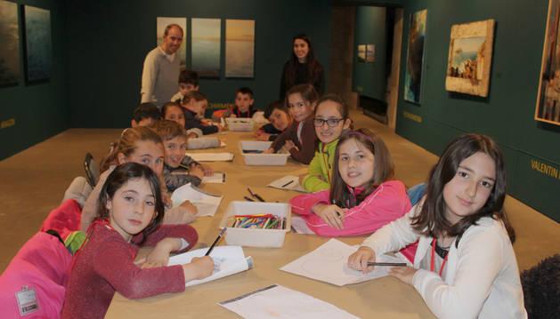 Imagen de los alumnos con los monitores del taller trabajando en la exposición Paisajes marinos.