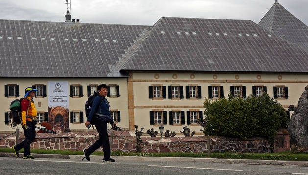 Dos peregrinos pasan frente al albergue de peregrinos de Roncesvalles.
