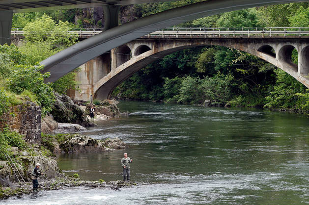 Dos pescadores tienden sus cañas en el río Bidasoa, bajo el arco del puente que cruza Endarlatsa, en el límite con Guipúzcoa.