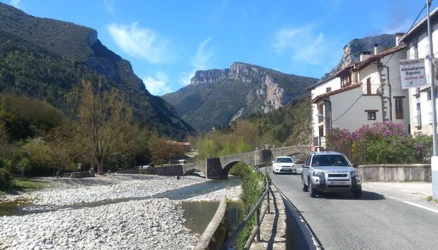 Dos vehículos circulan por la travesía de Burgui, junto al puente.