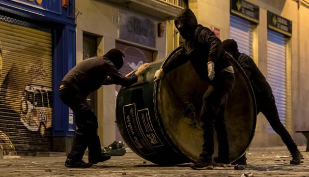 Imagen de tres encapuchados volcando un contenedor durante los incidentes registrados en la calle Chapitela.