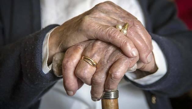 Una anciana navarra apoya sus manos en un bastón.