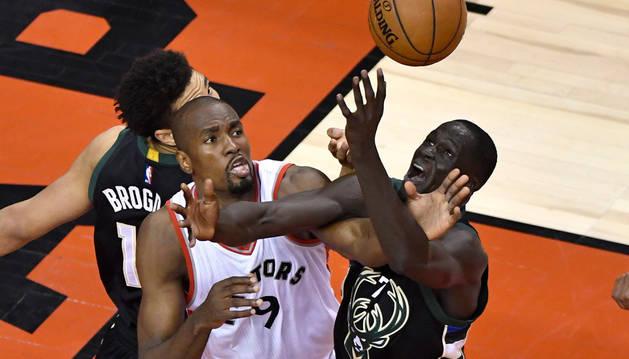 El jugador de Raptors Serge Ibaka (c) disputa el balón con thon Maker (d), de Bucks.