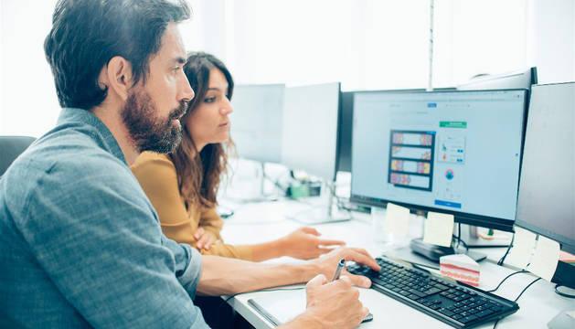 foto de dos empleados de una oficina frente a un ordenador