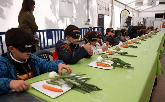 Varios alumnos del colegio público Huertas Mayores de Tudela intentan adivinar qué tipo de verdura tienen en sus manos durante el taller.