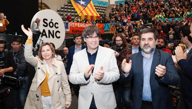 Foto de Carles Puigdemont (c), junto al presidente de la entidad soberanista, Jordi Sánchez (d), y la presidenta del Parlament, Carme Forcadell (i), durante la clausura de la asamblea general de la ANC.