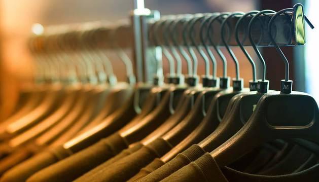 Imagen de varias prendas de ropa en perchas.