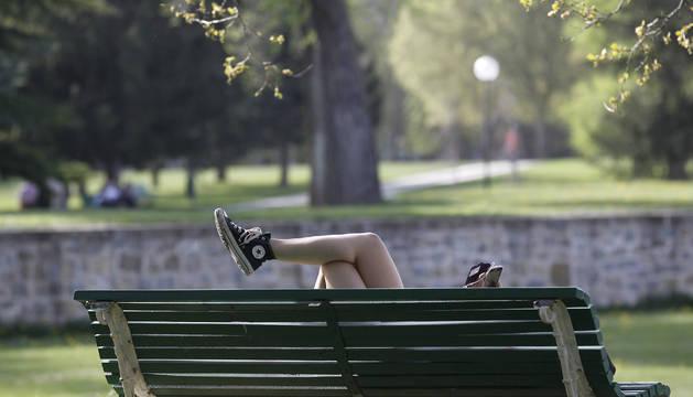 Una joven descansa en un banco de la Vuelta del Castillo y consulta el móvil.