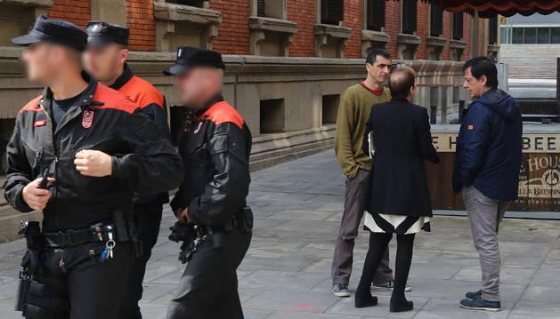 La presidenta Uxue Barkos, hablando ayer de la Ley de Policías con Carlos Couso y Rubén Velasco (Podemos) junto al edificio del Parlamento, coincidiendo con el paso de agentes de la Policía Foral.