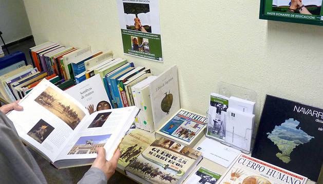 Un alumno ojea uno de los libros solidarios. Junto a ellos unos sobres y un buzón permiten hacer los donativos.