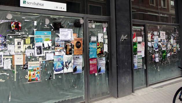 Decenas de carteles publicitarios llenan el escaparate de un local comercial de la calle Bergamín.