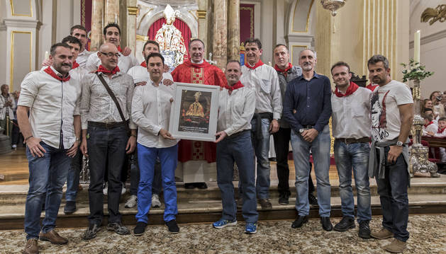 Agentes de Policía Foral y el párroco Javier Leoz, en la capilla de San Fermín con el retrato del santo regalo de la parroquia.