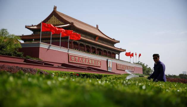 Un jardinero en la plaza de Tiananmen en Pekín.