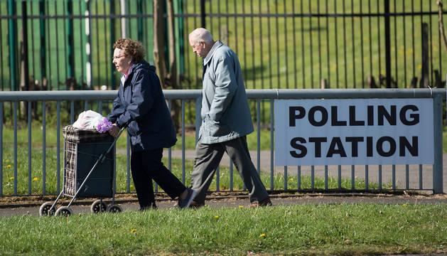 Dos personas, junto a un colegio electoral en Manchester.