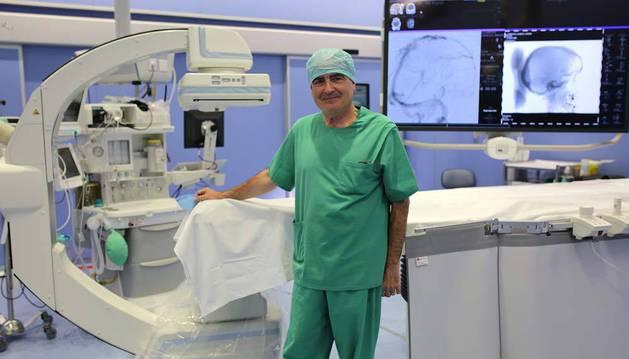 Imagen del doctor José Ignacio Bilbao posando en un quirófano híbrido de la Clinica Universidad de Navarra, junto a un equipo de radiología robotizado.