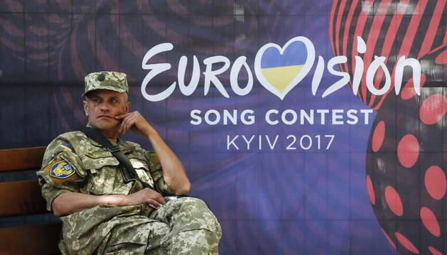 Imagen de un soldado ucraniano descansa junto a un cartel que promociona el festival de Eurovisión.