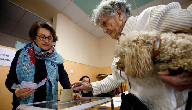 Una mujer mete la papeleta en una urna en la segunda vuelta de las elecciones presidenciales de Francia.