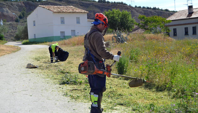 Imagen de trabajadores de la brigada medioambiental desbrozando unos terrenos frente al punto limpio.