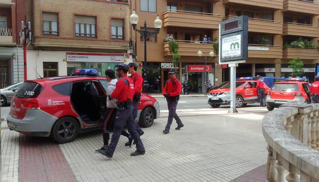 Policías forales se llevan a un detenido. Los otros dos fueron trasladados en los dos coches de la dcha.
