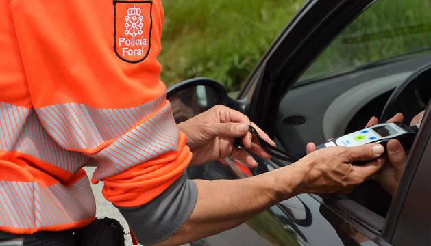 Un agente de la Policía Foral realiza una prueba de alcoholemia.
