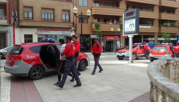 Agentes de Policía Foral llevan a uno de los detenidos al coche patrulla en el Paseo de Invierno de Tudela.