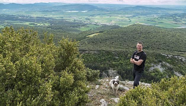 Iñaki Etxeberria, el viernes, en la Peña Azanza (1.075 m.), con su perro Milou. Al fondo, Arizala y el pantano de Alloz.