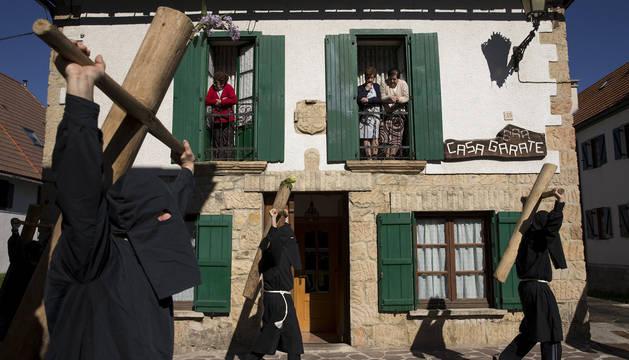 Unas mujeres miran por la ventana mientras los romeros pasan por Burguete.