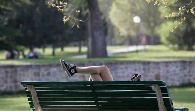Una joven escucha música en su teléfono móvil tumbada en un banco de Pamplona.
