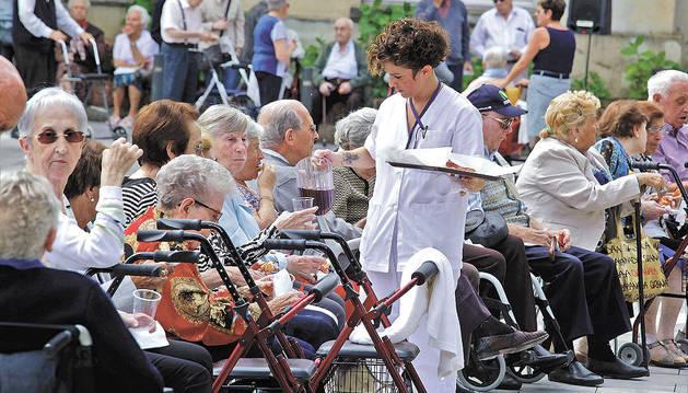 Una trabajadora de Casa de la Misericordia reparte sangría y queso del roncal a los mayores.