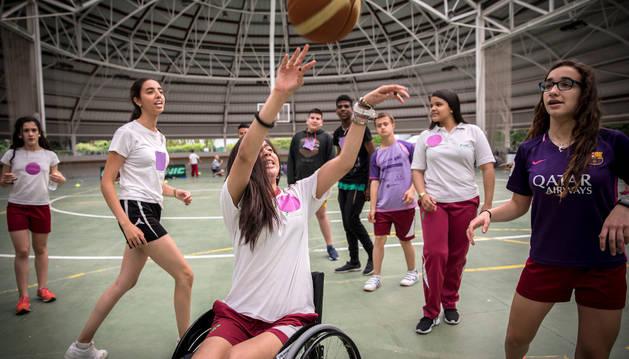 Imagen de un grupo de alumnas jugando a baloncesto en silla de rueda para ponerse en la piel de las personas con discapacidad.