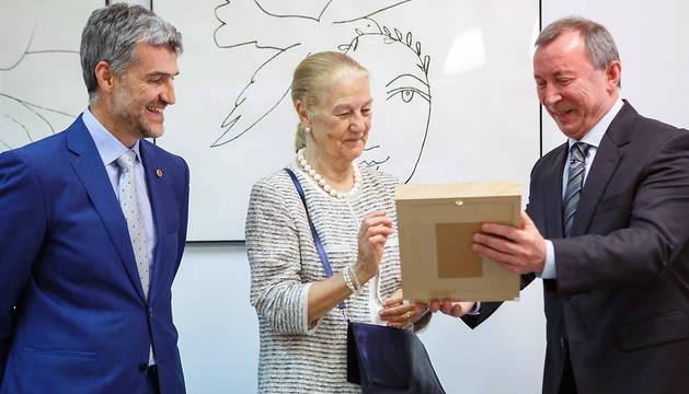 La viuda de Fernando Redón, María Castiella, recibe el retrato de quien fue su marido de manos de Joaquín Ansa, ante la mirada del rector, Alfonso Carlosena (izq.).