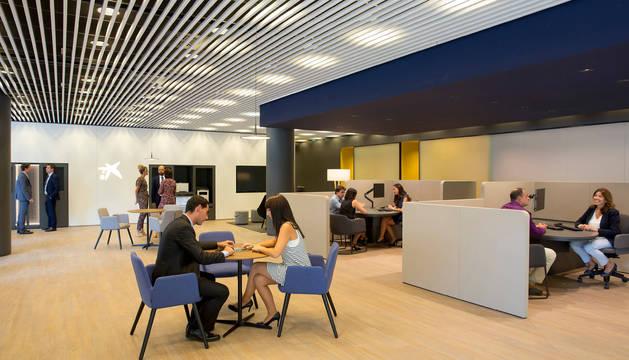Clientes son atendidos en una oficina de CaixaBank. Esta entidad ya ha formado a 247 trabajadores.