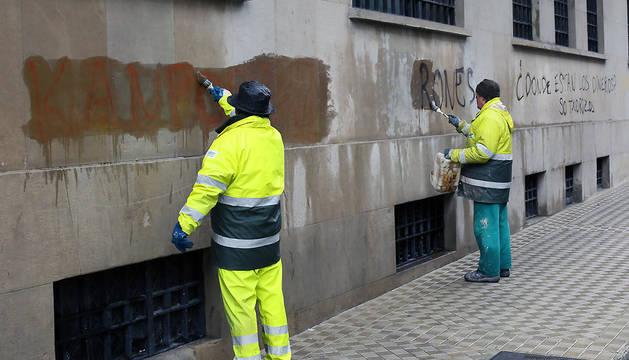 Imagen de unos operarios limpiando otras pintadas.