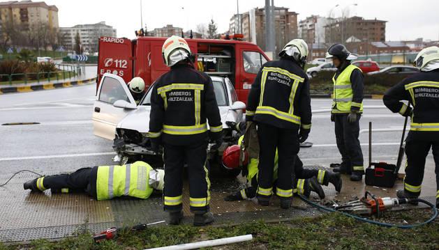 Bomberos actúan con un vehículo implicado en un siniestro en Pamplona.