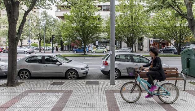 Una ciclista por la acera de Pío XII, junto al cordón de aparcamientos que se propone suprimir.