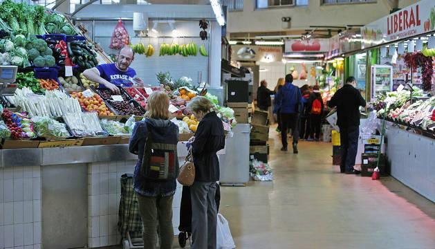A la izquierda, dos mujeres realizan compras en uno de los puestos de fruta y verdura del mercado del Ensanche. Al fondo, otro grupo de personas espera su turno.