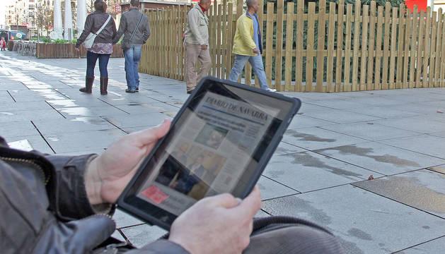 Una persona navega por Internet desde la calle Carlos III de Pamplona.