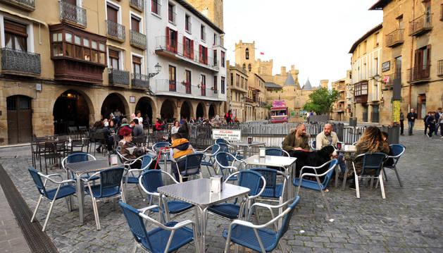Varias personas en una de las terrazas ubicadas en la plaza de Carlos III, en Olite.