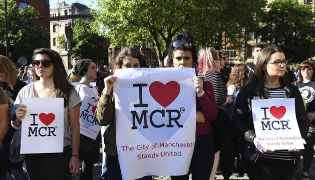 Varias personas asisten a una vigilia por los 22 fallecidos en atentado del pabellón Manchester Arena.