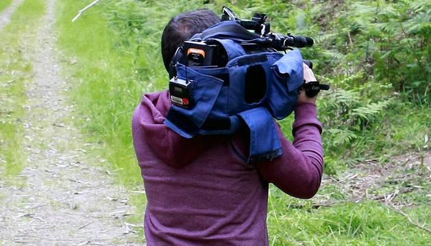 Un cámara de televisión toma imágenes en una zona boscosa.