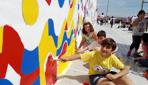 Foto de tres niños pintan parte del mural de más de 100 m2 dibujado por Loperena para el proyecto Landarte.