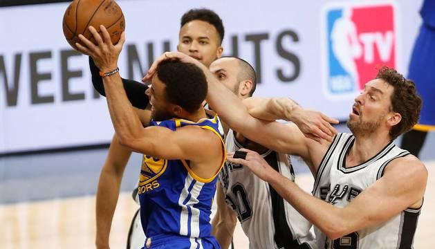 Pau Gasol trata de detener el avance de Stephen Curry durante el último parte entre Warriors y Spurs