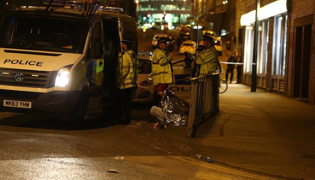 Una mujer es vista sentada en una calle cerca al Manchester Arena, junto a un grupo de policías, luego de dos explosiones registradas cerca al lugar en Manchester,