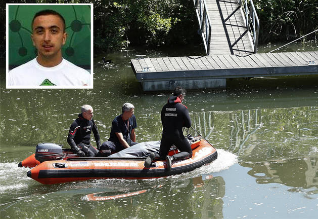 Foto de Varios bomberos sobre una lancha trasladan el cadáver que ha sido hallado en el río Arga.