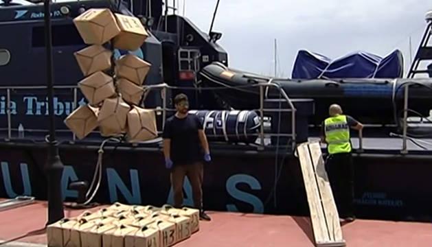 Los miembros de Agencia Tributaria descargan los fardos del velero.