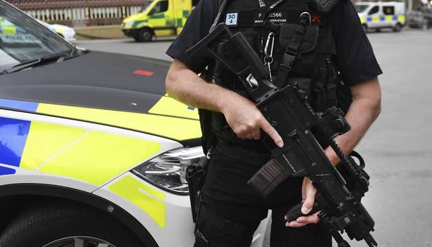 Foto detalle del arma de un policía británico mientras monta guardia en las calles de Manchester.
