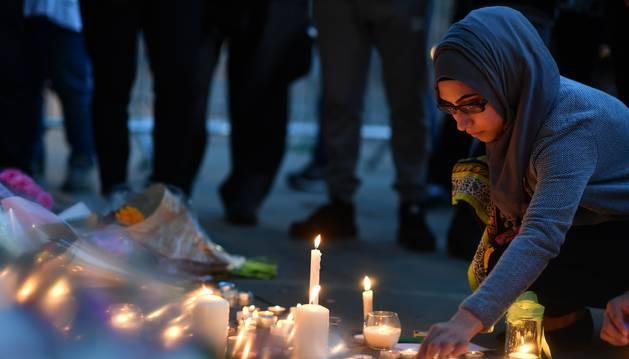Foto de una mujer enciende velas en uno de los tributos florales en Albert Square, en Manchester.