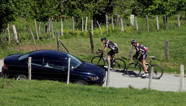 Imagen de dos ciclistas cruzándose con un vehículo en la carretera de acceso a Beruete.