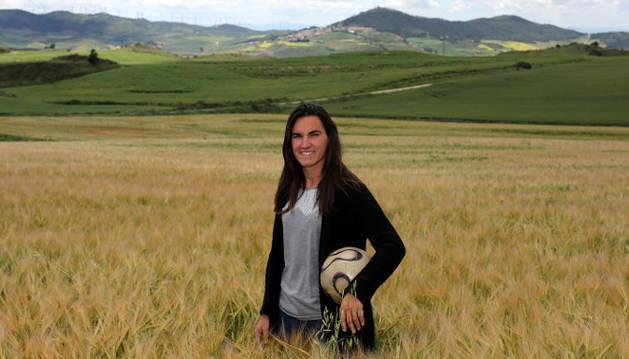 En medio de un campo de cereal en Biurrun, Eunate Arraiza Otazu, de 25 años de edad, sostiene un balón en un brazo.